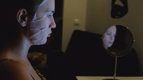 Νέα γυναίκα με την του προσώπου μάσκα φύλλων απόθεμα βίντεο