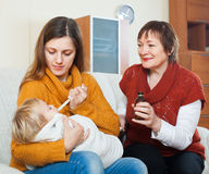 Νέα γυναίκα με την ώριμη μητέρα που φροντίζει για το μωρό Στοκ Φωτογραφίες