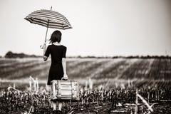 Νέα γυναίκα με τη βαλίτσα και την ομπρέλα στοκ φωτογραφία