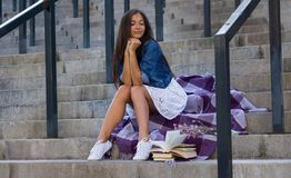 Νέα γυναίκα με τη δέσμη των βιβλίων που κάθεται στα σκαλοπάτια σε αστικό στο σακάκι τζιν παντελόνι στοκ φωτογραφίες με δικαίωμα ελεύθερης χρήσης
