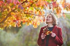 Νέα γυναίκα με τη δέσμη των ζωηρόχρωμων φύλλων φθινοπώρου στοκ εικόνες