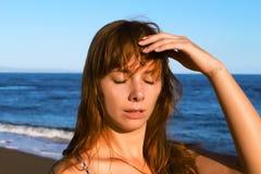 Νέα γυναίκα με τη θερμοπληξία Ηλίαση σε μια παραλία Υγιής τρόπος ζωής στις διακοπές Στοκ Εικόνα