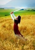 Νέα γυναίκα με τη διακοσμητική διαθέσιμη στάση φορεμάτων και ξιφών σε έναν τομέα σίτου με το ηλιοβασίλεμα Φυσική ανασκόπηση Στοκ φωτογραφίες με δικαίωμα ελεύθερης χρήσης