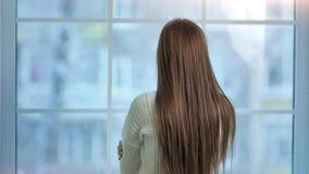 Νέα γυναίκα με τη μακριά όμορφη τρίχα που κοιτάζει στην παγωμένη μεγάλη πίσω άποψη παραθύρων φιλμ μικρού μήκους