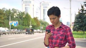 Νέα γυναίκα με τη μαύρη σύντομη δακτυλογράφηση τρίχας στο τηλέφωνο και την αναμονή το ταξί ή την έρευνα του λεωφορείου, χαμόγελο, απόθεμα βίντεο