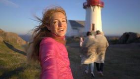 Νέα γυναίκα με τη μεγάλη οικογένειά της που οδηγεί το σύζυγό της που περπατά προς τη δύσκολη βόρεια παραλία απόθεμα βίντεο