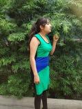 νέα γυναίκα με τη μυρωδιά φορεμάτων και σχετικά με τα φύλλα ενός φυτού Στοκ εικόνες με δικαίωμα ελεύθερης χρήσης