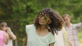 Νέα γυναίκα με τη σγουρή τρίχα που χορεύει, κεφάλι τινάγματος στο φεστιβάλ μουσικής, σε αργή κίνηση φιλμ μικρού μήκους