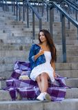 Νέα γυναίκα με τη συνεδρίαση βιβλίων στα σκαλοπάτια σε αστικό στο σακάκι τζιν παντελόνι στοκ φωτογραφίες