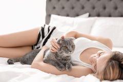 Νέα γυναίκα με τη χαριτωμένη γάτα κατοικίδιων ζώων της στο κρεβάτι στοκ εικόνα με δικαίωμα ελεύθερης χρήσης