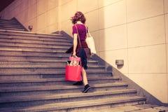 Νέα γυναίκα με τις αγορές που περπατούν επάνω τα σκαλοπάτια Στοκ εικόνα με δικαίωμα ελεύθερης χρήσης