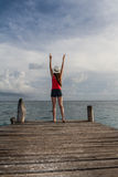 Νέα γυναίκα με τις ανοικτές αγκάλες που απολαμβάνει το ηλιοβασίλεμα στη θάλασσα Στοκ Εικόνες