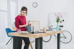 Νέα γυναίκα με τις απεικονίσεις δουλεύοντας τον πίνακα στοκ εικόνα