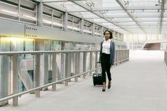 Νέα γυναίκα με τις αποσκευές που περπατά στο τερματικό Στοκ εικόνα με δικαίωμα ελεύθερης χρήσης