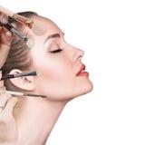 Νέα γυναίκα με τις βούρτσες makeup στοκ εικόνες
