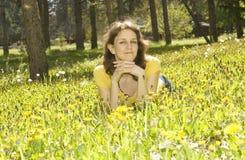 Νέα γυναίκα με τις κίτρινες πικραλίδες στοκ εικόνες