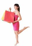 Νέα γυναίκα με τις τσάντες αγορών στο λευκό Στοκ Εικόνες