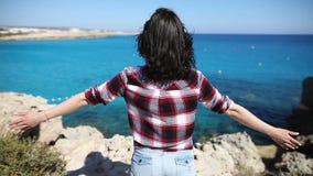 Νέα γυναίκα με τον αέρα στην τρίχα της που αυξάνει τα χέρια της πάνω από τον απότομο βράχο επάνω από την όμορφη θάλασσα φιλμ μικρού μήκους
