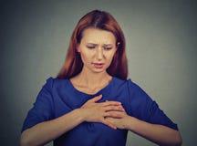 Νέα γυναίκα με τον πόνο στηθών σχετικά με το στήθος που απομονώνεται στο γκρίζο υπόβαθρο τοίχων στοκ εικόνα
