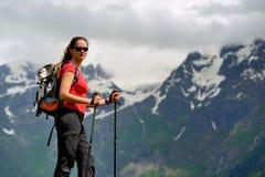 Νέα γυναίκα με τους πόλους σακιδίων πλάτης και οδοιπορίας στα βουνά Στοκ Εικόνες