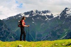 Νέα γυναίκα με τους πόλους σακιδίων πλάτης και οδοιπορίας στα βουνά Στοκ Φωτογραφίες