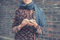 Νέα γυναίκα με το έξυπνο τηλέφωνο στην οδό Στοκ Φωτογραφίες