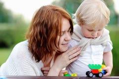 Νέα γυναίκα με το γιο μικρών παιδιών του που παίζει με τους ζωηρόχρωμους πλαστικούς φραγμούς Στοκ φωτογραφία με δικαίωμα ελεύθερης χρήσης