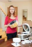 Νέα γυναίκα με το ηλεκτρικό δοχείο αγγείων στον πίνακα στην κουζίνα της Στοκ Φωτογραφία