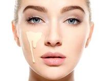Νέα γυναίκα με το καλλυντικό ίδρυμα στο δέρμα στοκ εικόνες