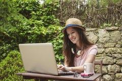 Νέα γυναίκα με το καπέλο αχύρου που λειτουργεί με το lap-top υπαίθρια Στοκ Εικόνα