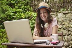 Νέα γυναίκα με το καπέλο αχύρου που λειτουργεί με το lap-top υπαίθρια Στοκ φωτογραφία με δικαίωμα ελεύθερης χρήσης