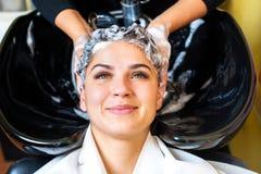 Νέα γυναίκα με το κεφάλι πλύσης κομμωτών στο κομμωτήριο στοκ εικόνα
