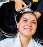 Νέα γυναίκα με το κεφάλι πλύσης κομμωτών στο κομμωτήριο στοκ φωτογραφίες με δικαίωμα ελεύθερης χρήσης
