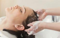 Νέα γυναίκα με το κεφάλι πλύσης κομμωτών στο κομμωτήριο στοκ εικόνες με δικαίωμα ελεύθερης χρήσης