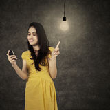 Νέα γυναίκα με το κινητό τηλέφωνο κάτω από το lightbulb Στοκ φωτογραφία με δικαίωμα ελεύθερης χρήσης