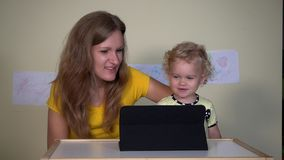 Νέα γυναίκα με το κορίτσι παιδιών της που φαίνεται αστεία κινούμενα σχέδια στον υπολογιστή ταμπλετών φιλμ μικρού μήκους