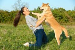 Νέα γυναίκα με το λατρευτό σκυλί Akita Inu στοκ φωτογραφία