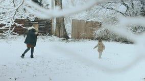 Νέα γυναίκα με το μακροχρόνιο παιχνίδι ξανθών μαλλιών με το γιο της το χειμώνα στο χιονώδες πάρκο 4k φιλμ μικρού μήκους
