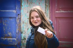 Νέα γυναίκα με το μεγάλο χαμόγελο που επιδεικνύει την κενή επαγγελματική κάρτα Ρηχό βάθος του τομέα, εστίαση στην κάρτα Στοκ εικόνες με δικαίωμα ελεύθερης χρήσης