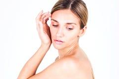 Νέα γυναίκα με το ομαλό δέρμα που κρατά το χέρι της κοντά στο μάγουλο και που κοιτάζει κάτω στοκ φωτογραφίες με δικαίωμα ελεύθερης χρήσης