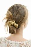 Νέα γυναίκα με το περιστασιακό ακατάστατο hairdo κουλουριών στοκ φωτογραφία με δικαίωμα ελεύθερης χρήσης