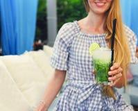 Νέα γυναίκα με το ποτήρι της λεμονάδας Στοκ Φωτογραφίες
