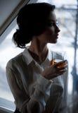 Νέα γυναίκα με το ποτήρι του ουίσκυ στο υπόβαθρο του παραθύρου Στοκ φωτογραφία με δικαίωμα ελεύθερης χρήσης