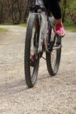 Νέα γυναίκα με το ποδήλατο βουνών σε έναν βρώμικο δρόμο στοκ φωτογραφίες