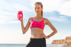 Νέα γυναίκα με το ρόδινο μπουκάλι στην παραλία Στοκ εικόνες με δικαίωμα ελεύθερης χρήσης