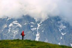 Νέα γυναίκα με το σακίδιο πλάτης στο κόκκινο σακάκι στα βουνά Στοκ Φωτογραφία
