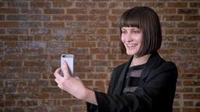 Νέα γυναίκα με το σύντομο κούρεμα που έχει την τηλεοπτική κλήση μέσω του τηλεφώνου κυττάρων της, απομονωμένη στο υπόβαθρο τούβλου φιλμ μικρού μήκους