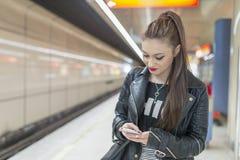Νέα γυναίκα με το τηλέφωνο στον υπόγειο Στοκ Φωτογραφία