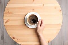 Νέα γυναίκα με το φλυτζάνι του εύγευστου καφέ στον πίνακα, τοπ άποψη στοκ φωτογραφία
