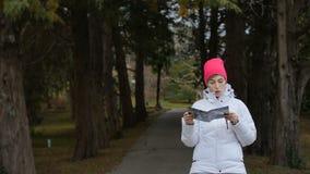 Νέα γυναίκα με το φυλλάδιο στο δάσος απόθεμα βίντεο